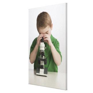 Caucasian boy peering into microscope canvas print