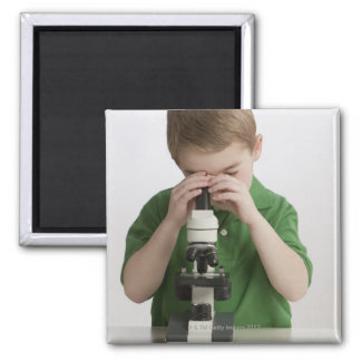 Caucasian boy peering into microscope magnet