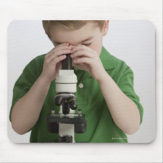 Caucasian boy peering into microscope mouse pad