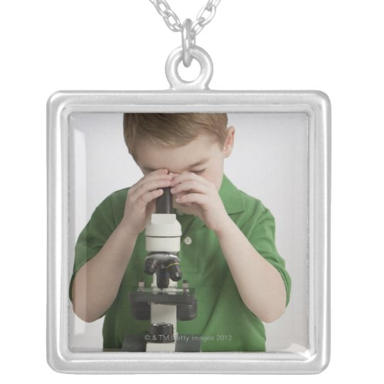 Caucasian boy peering into microscope silver plated necklace