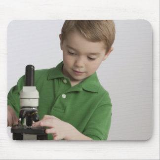 Caucasian boy using microscope mouse pad