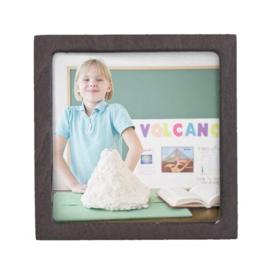 Caucasian girl standing with model volcano jewelry box