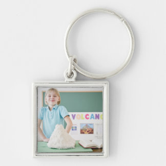 Caucasian girl standing with model volcano keychains