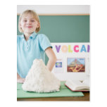 Caucasian girl standing with model volcano postcard