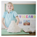 Caucasian girl standing with model volcano large square tile