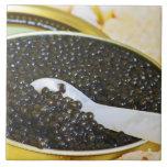 Caviar negro y una cuchara de nacarado a azulejo cuadrado grande