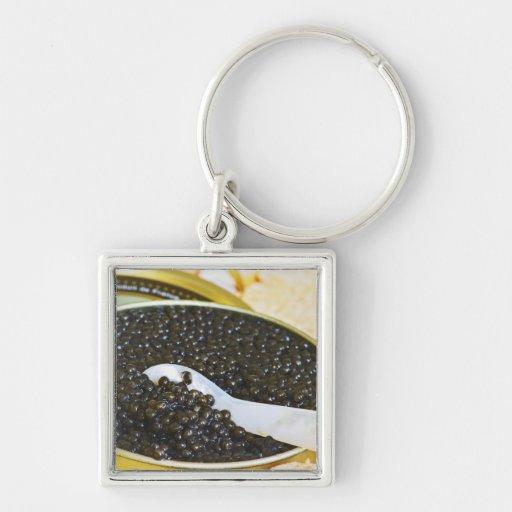 Caviar negro y una cuchara de nacarado a llavero cuadrado plateado