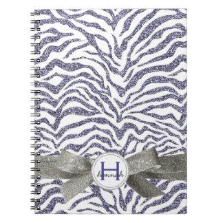 Cebra púrpura de la mirada reluciente linda con el libro de apuntes con espiral