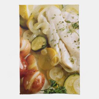 Cena cocida de los pescados toalla de cocina