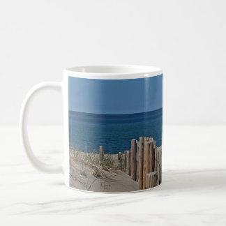 Cerca de la playa y playa arenosa taza