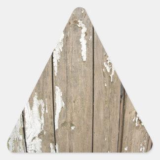 Cerca de madera vieja con la pintura exfoliated pegatina triangular