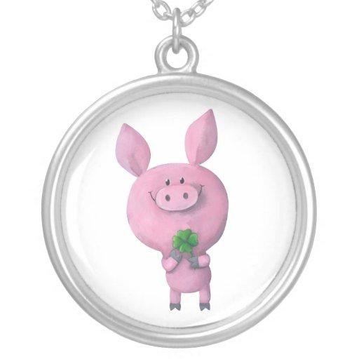 Cerdo afortunado con el trébol afortunado de cuatr collares