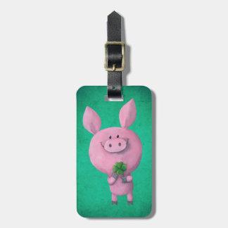 Cerdo afortunado con el trébol afortunado de cuatr etiquetas maletas