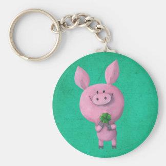Cerdo afortunado con el trébol afortunado de cuatr llaveros