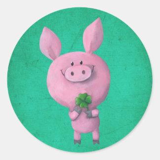 Cerdo afortunado con el trébol afortunado de cuatr etiqueta redonda
