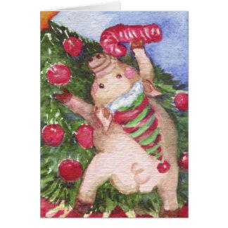 Cerdo con un bastón de caramelo que admira el tarjeta de felicitación