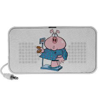 cerdo divertido en una dieta que come un buñuelo e altavoces de viaje