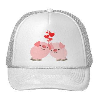 Cerdos lindos del dibujo animado en gorra del amor