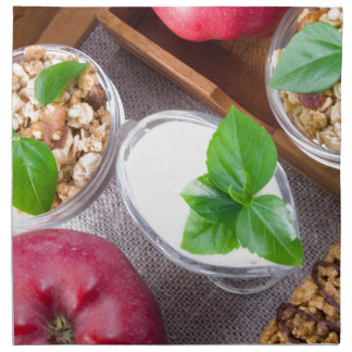 Cereal with walnuts and raisins, yogurt and apples napkin