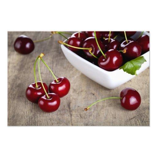 Cerezas dulces en cuenco en fondo de la tabla impresiones fotográficas