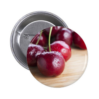 Cerezas en el botón de la tabla de cortar pin redondo de 2 pulgadas