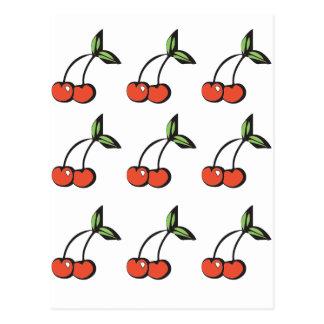 Cerezas rojas brillantes con el modelo verde de postales
