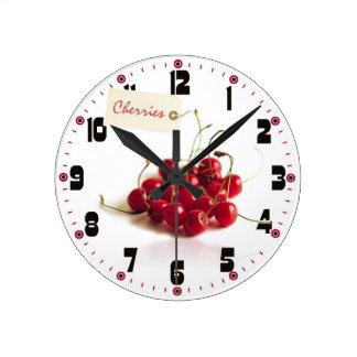 Cerezas rojas con el reloj de la etiqueta