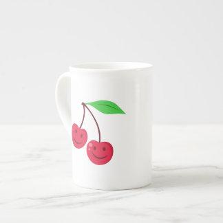 Cerezas rojas sonrientes taza de té