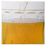 Cerveza de colada en la taza de cristal, extremo, azulejo cuadrado grande