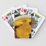 Cerveza vertido en el vidrio baraja cartas de poker