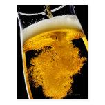 Cerveza vertido en el vidrio postal