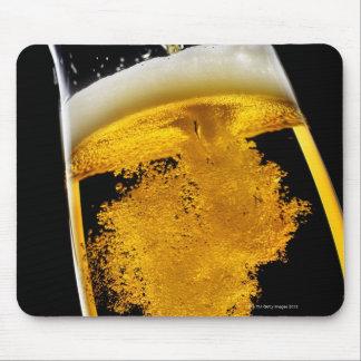 Cerveza vertido en el vidrio alfombrilla de raton