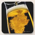 Cerveza vertido en el vidrio, tiro del estudio posavasos