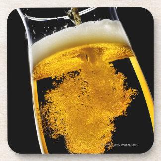 Cerveza vertido en el vidrio, tiro del estudio posavasos de bebida