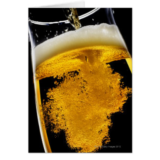 Cerveza vertido en el vidrio, tiro del estudio tarjeta de felicitación