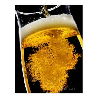 Cerveza vertido en el vidrio, tiro del estudio tarjetas postales