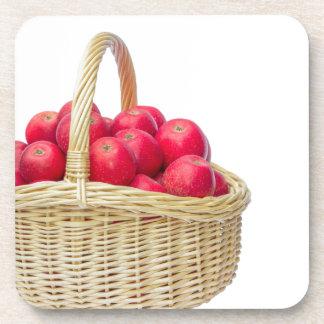 Cesta llena con las manzanas rojas posavasos