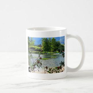 Charca secreta en un día soleado hermoso taza básica blanca
