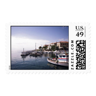 Charming little boats sail into a port postage