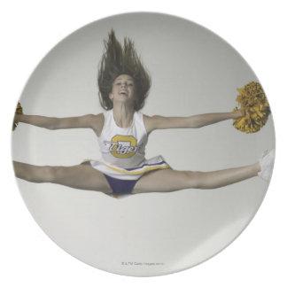 Cheerleader doing splits in mid air dinner plates