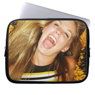Cheerleader flipping hair, laughing, surrounded laptop sleeves