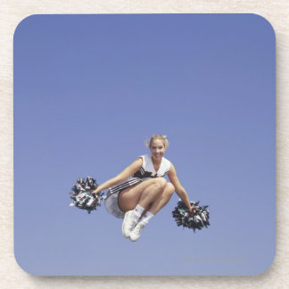 Cheerleader jumping, low angle view, portrait drink coaster