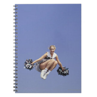 Cheerleader jumping, low angle view, portrait notebook