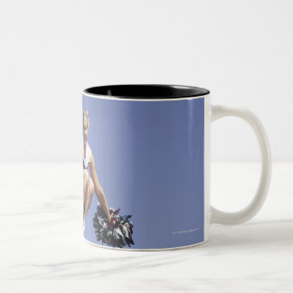Cheerleader jumping, low angle view, portrait Two-Tone coffee mug