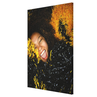 Cheerleader laughing, surrounded by pompoms, canvas print
