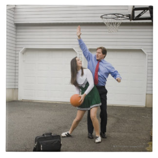 Cheerleader playing basketball with her father ceramic tile