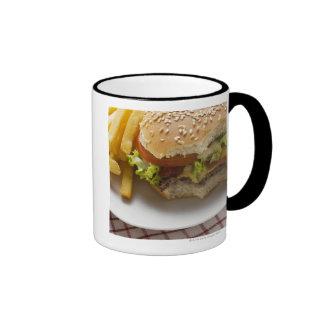 Cheeseburger, mordeduras tomadas, con los micropro taza de café