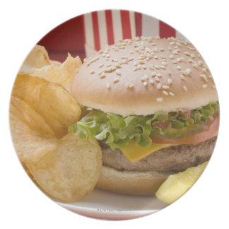 Cheeseburger with potato crisps and gherkin dinner plate