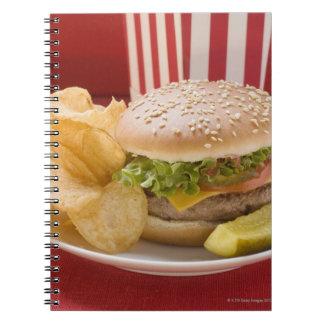 Cheeseburger with potato crisps and gherkin spiral notebook