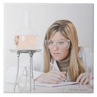 Chemist looking at Bunsen burner Ceramic Tile